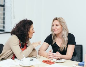 Two women having a chat over coffee and cake