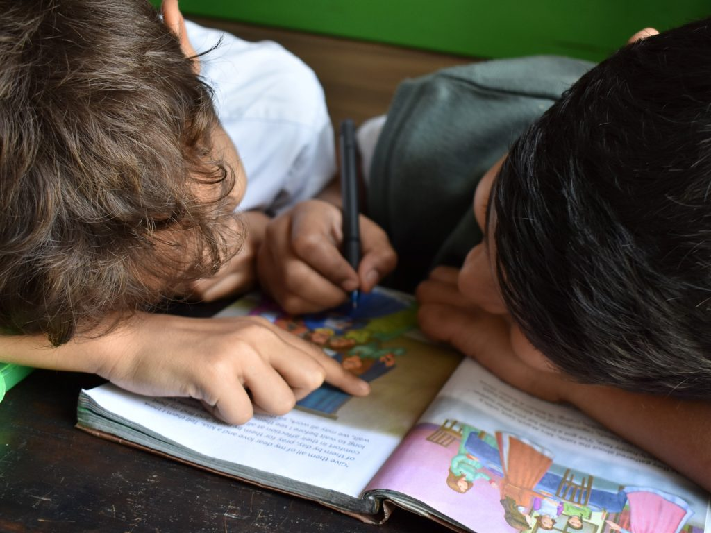 Children reading a book together